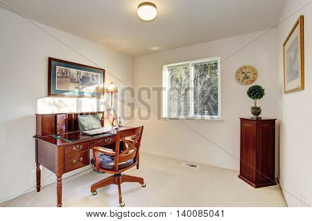 Old fashioned desk with drawers in home office interior with one window and beige walls. Northwest USA