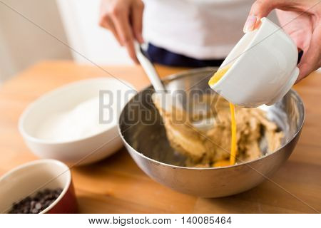 Adding egg inside the dough for making cookies