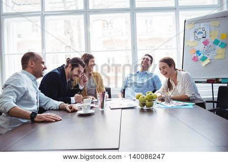 Cheerful colleagues discussing in meeting room at creative office