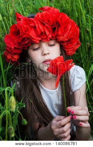 Girl with wreath  in the poppy field