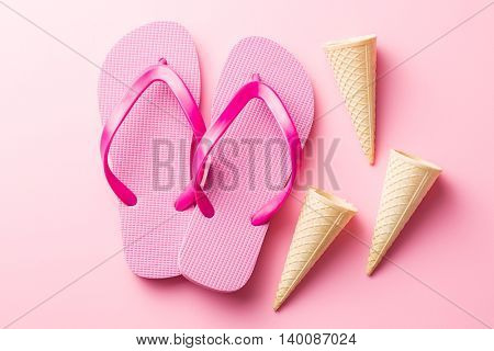 Flip flops and wafer cones on pink background.