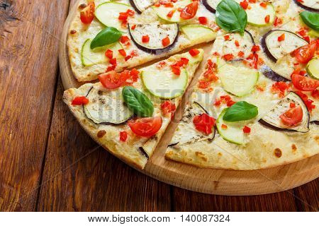 Delicious italian vegetarian pizza with cherry tomatoes, peppers, aubergines and zucchini - thin pastry crust at wooden table background, one piece cut