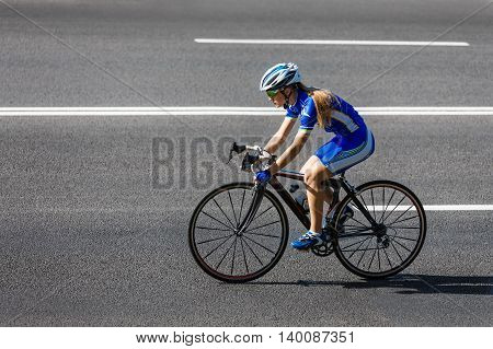 Female sportsman cyclist riding racing bicycle. Woman cycling on countryside road or highway. Training for triathlon or cycling competition.