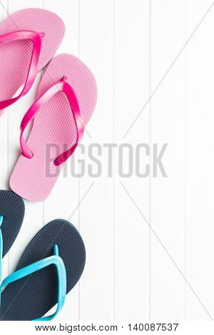Pink and blue flip flops on white floor.
