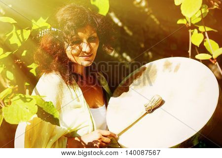 beautiful shamanic girl playing on shaman frame drum in the nature. solar light effect