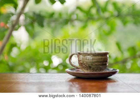 Hot coffee cup on the wooden table with bokeh background in coffee shop