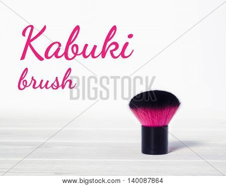 Still life make up pink kabuki brush on a white wooden background closeup with copy-space