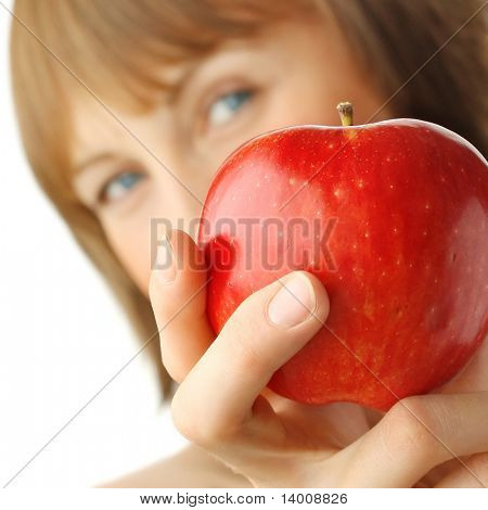 Young woman with enigmatic glance holding red apple