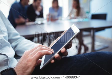 Midsection of businessman using digital tablet against coworkers in meeting room at office