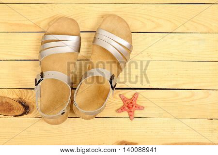 pair of sandals on wooden surface top view