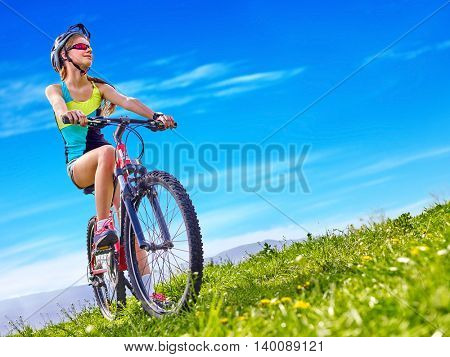 Bicycle child. Girl rides bicycle. Girl in cycling. Bicycle is good for child health. Cyclist look up on blue sky.