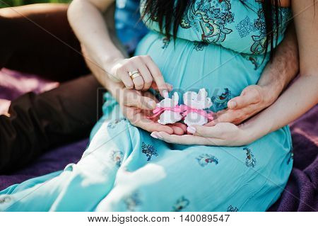 Happy Pregnant Couple. Close Up Hand With Baby Girl Shoes