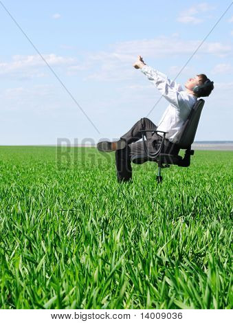 Stretching man on chair in green field