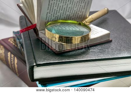 magnifying glass on a stack of books background
