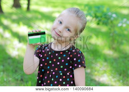 Russian child with a credit card in nature