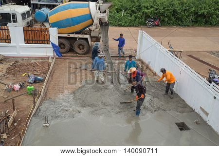 A Cement Truck And Worker Are Pouring Cement To New Floor