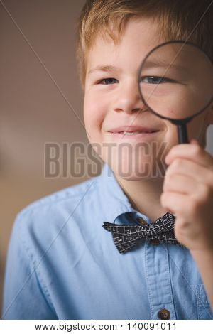 Portrait of cute schoolboy kid in blue shirt looking through a magnifier. Child watching through magnifying glass. Indoors. Education and learning concept.