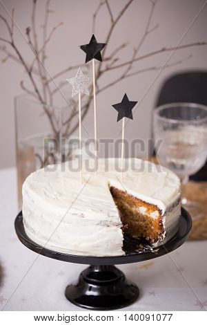 Close up of delicious homemade birthday white cake decorated with silver stars on the table. Baking at home for events. Cooking sweet cake for holidays. indoors.Carrot cake with white icing.