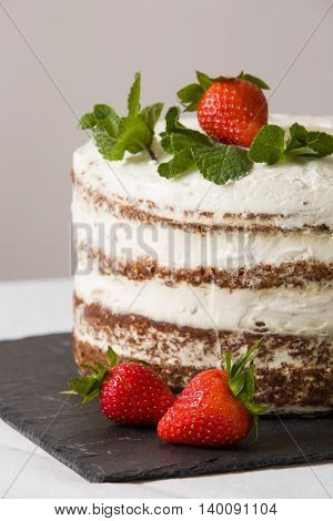 Delicious white cream icing cake with strawberry on the black board. Naked cake with cream decorated with strawberries and mint.