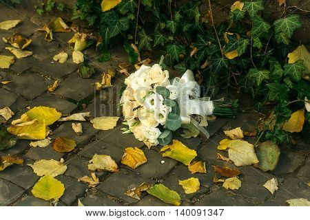 Bridal bouquet of beautiful creamy roses laying on ground in autumn