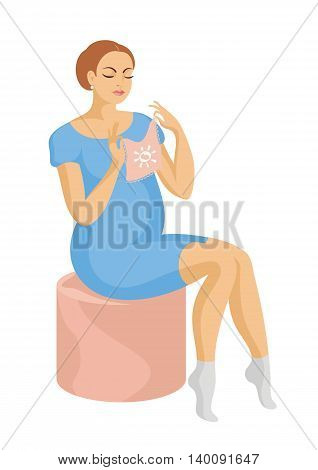 young, beautiful future mother in a blue dress sits on a padded stool and looking at a children's jacket