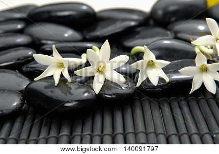 Set of black stones with white flower on bamboo mat