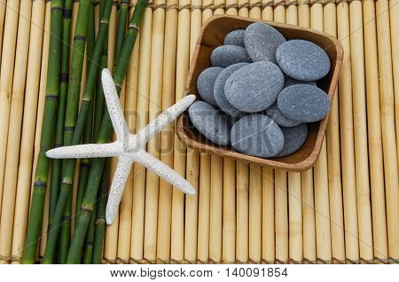 Stones in bowl with starfish .bamboo grove on mat