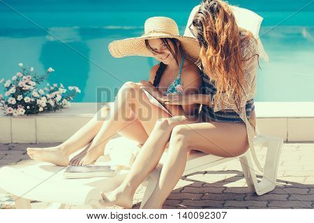 young pretty woman in glasses near small girl in straw hat reading book at swimming pool with blue water sunny summer vacation
