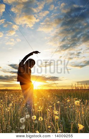 Young women doing exercises on field with grass under sunset light