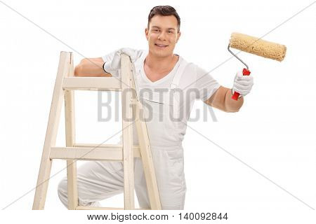 Studio shot of a cheerful young decorator holding a paint roller and standing on a ladder isolated on white background