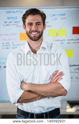 Portrait of confident businessman with arms crossed standing against whiteboard in office