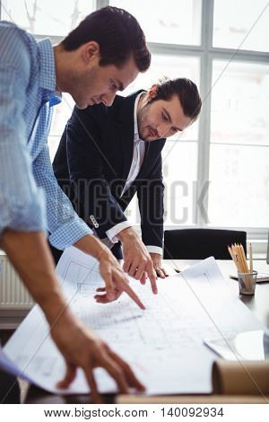 Interior designer discussing blueprint with male coworker in office