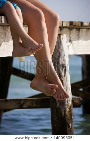 Mom and her child sitting on the wooden pier in the water and enjoying summer day. Bare feet of mother and her kid. Vacation by the sea. Outdoors.