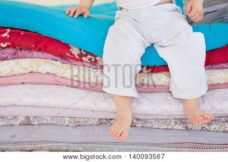 Small baby boy in white trousers sitting on a pile of colorful blankets and mattresses. Happy childhood. Leisure. Indoors. barefoot boy in the bedroom or kids room.