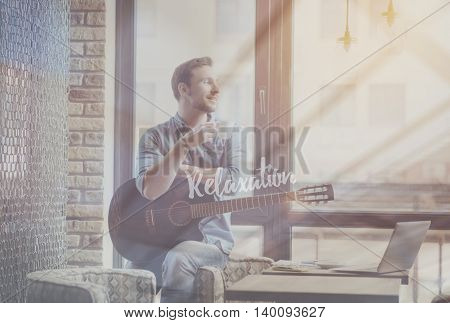Take it easy. Inspirational motivational image of relaxation with image of smiling man drinking coffee and holding guitar in a background