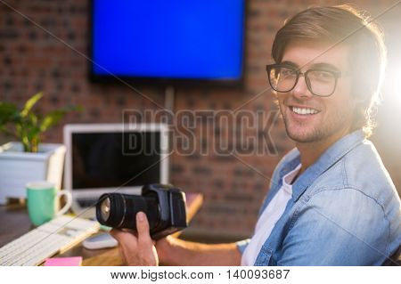 Portrait of smiling young man holding camera in creative office