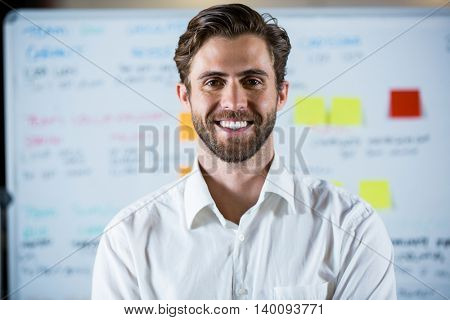 Portrait of confident businessman against whiteboard in meeting room
