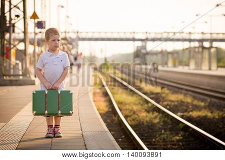Adorable little kid boy dressed in shorts and polo t-shirt on a railway station waiting for the train with retro old green suitcase. Ready for vacation. Young traveller on the platform.