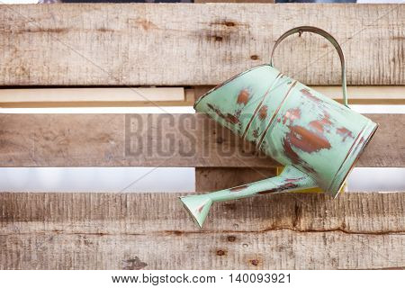 Details. Vintage metallic watering can by a wooden background. Old rustic watering can on the wooden wall.