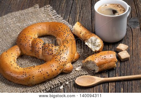 Soft pretzels with cup of hot coffee for breakfast on a rough fabric located on an old wooden table