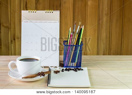 Coffee cupand note book with calendar on wooden table background. Business concept