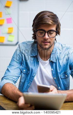 Young man using digital tablet and mobile phone in creative office