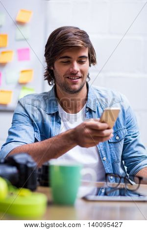 Young man using mobile phone in creative office