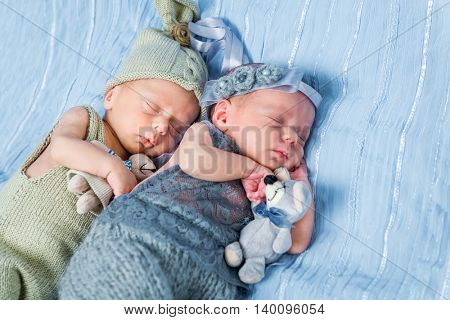 newborn twins  sleeping with toys on a blue blanket close up