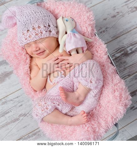 cute smiling newborn baby girl in a pink hat sleeping with a toy hare