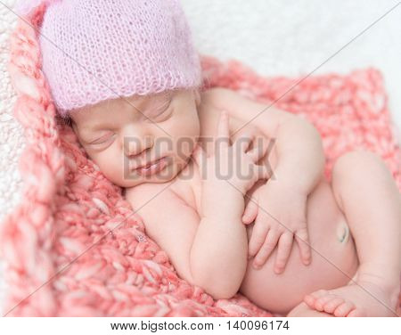 newborn baby girl in a pink hat sleeping