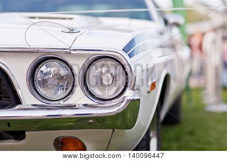Headlights of old white american muscle car with chrome bumper.