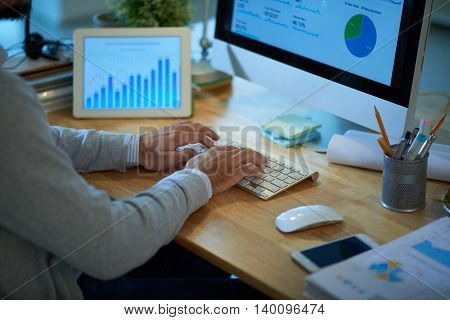 Hands of business executive analyzing information on computer screen