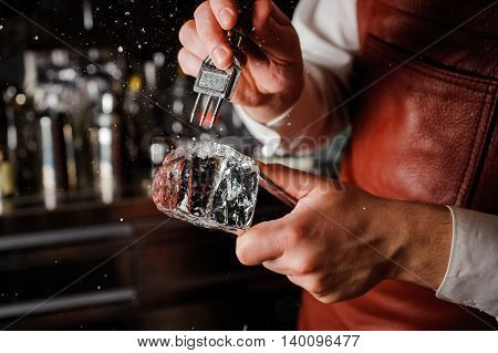 barman breaking ice with pick behind bar