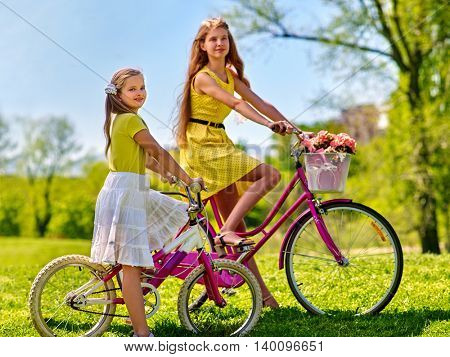 Bikes bicycle girl. Teenager girl and child wearing yellow polka dots dress keeps bicycle with flowers basket. Summer outdoor in park aganist blue sky.